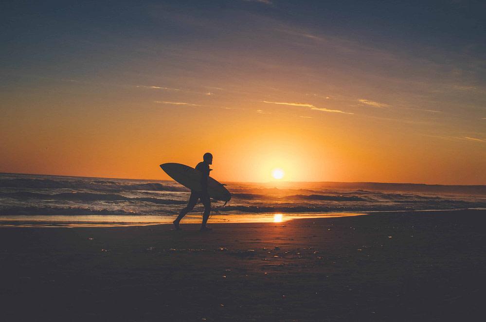 Intermediate level surfer with short board walking on the beach.