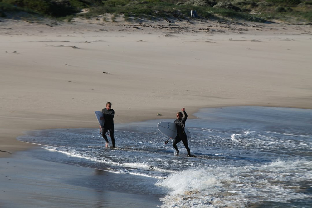 Two men surfing in cold water conditions